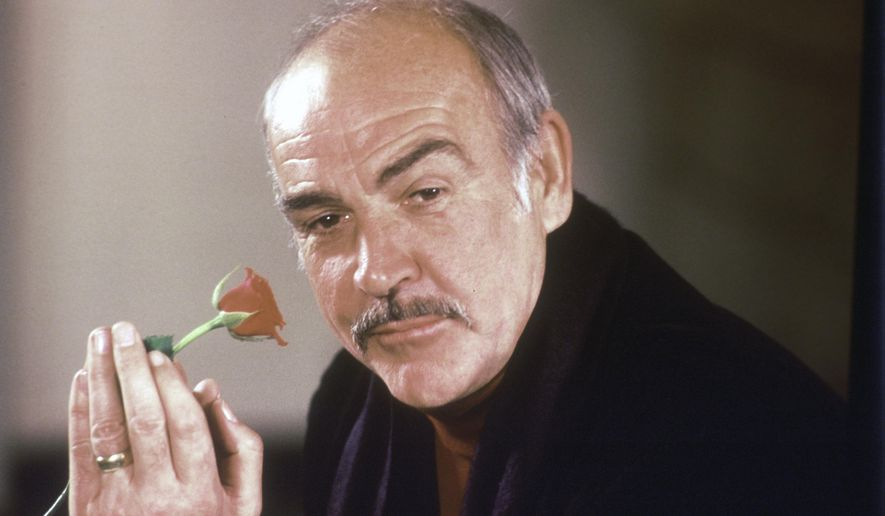 """In this Jan. 23, 1987, file photo, actor Sean Connery holds a rose in his hand as he talks about his new movie """"The Name of the Rose"""" at a news conference in London.  Scottish actor Sean Connery, considered by many to have been the best James Bond, has died aged 90, according to an announcement from his family. (AP Photo/Gerald Penny, File)"""