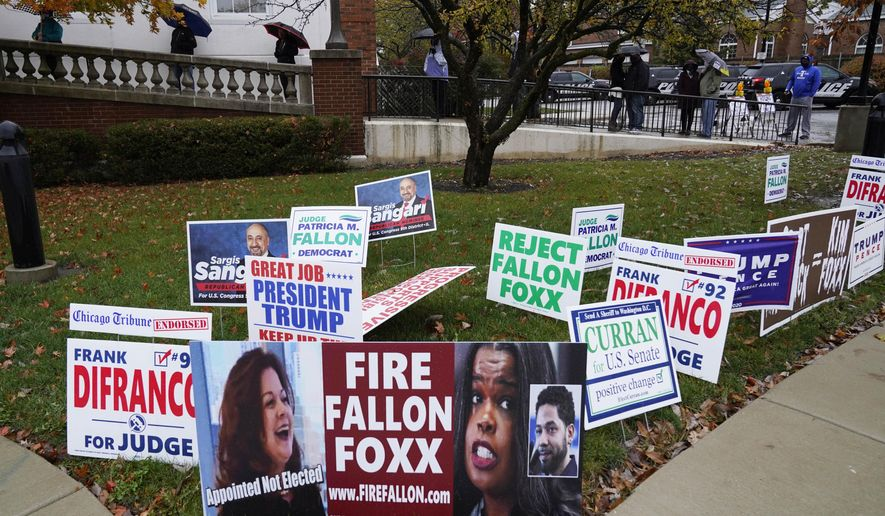 People wear masks as they wait in line during early voting at Park Ridge City Hall in Park Ridge, Ill., Friday, Oct. 23, 2020. The US early voting total in 2020 has already exceeded the number of early votes cast in 2016 and there are still 11 more days to go until Election Day. (AP Photo/Nam Y. Huh)