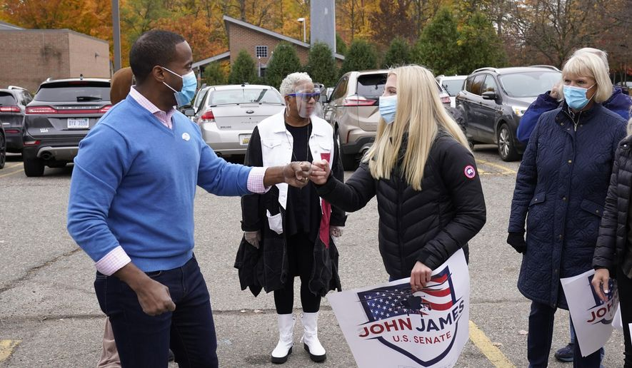 Republican U.S. Senate candidate John James, left, greets supporters in Farmington Hills, Mich., Monday, Oct. 26, 2020. (AP Photo/Paul Sancya) ** FILE **