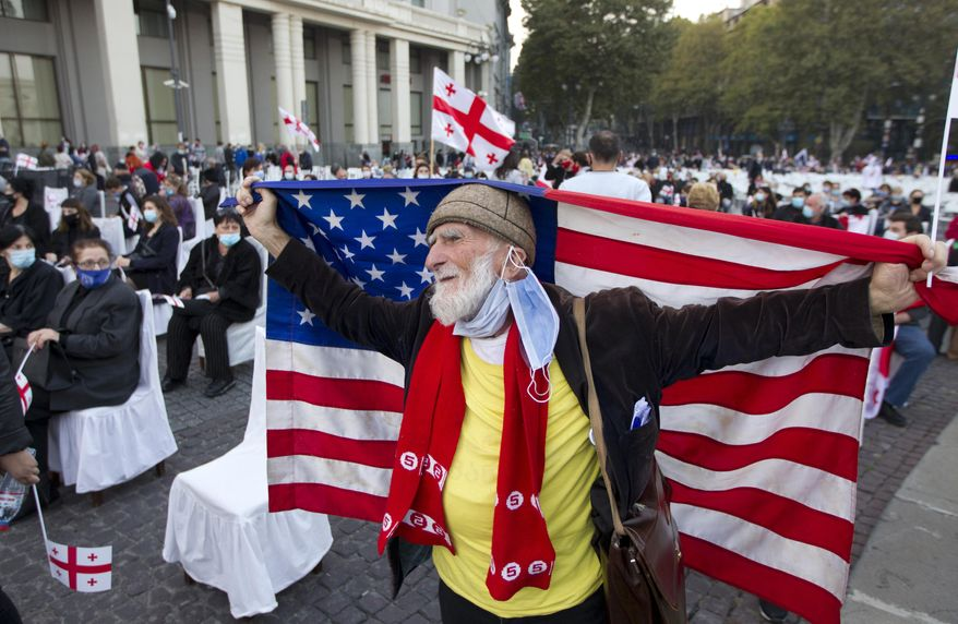 A supporters of the United National Movement party holds an American national flag as he attends a parliamentary election campaign rally in Tbilisi, Georgia, Thursday, Oct. 29, 2020. The parliamentary elections will take place in Georgia on Saturday, Oct. 31, 2020. (AP Photo/Shakh Aivazov)