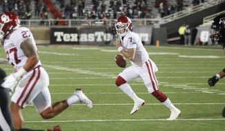 Oklahoma quarterback Spencer Rattler looks for an open receiver during the first half of the team's NCAA college football game against Texas Tech on Saturday, Oct. 31, 2020, in Lubbock, Texas. (AP Photo/Mark Rogers)