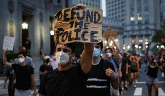 "This photo from Thursday, July 30, 2020, shows a demonstrator holding a sign that reads ""Defund the police"" during a protest march in New York. (AP Photo/John Minchillo) **FILE**"