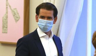 Austrian Chancellor Sebastian Kurz with a face mask walks at the federal chancellery in Vienna, Austria, Saturday, Oct. 31, 2020. The Austrian government has moved to restrict freedom of movement for people, in an effort to slow the onset of the COVID-19 coronavirus. (AP Photo/Ronald Zak)