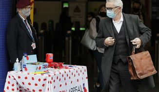 L Frank Plugge wears a mask and gloves as he sells poppies to raise money for the Royal British Legion annual poppy appeal in London, Thursday, Oct. 29, 2020. Around 100,000 people are catching the coronavirus every day in England, according to the latest Imperial College London study. (AP Photo/Kirsty Wigglesworth)