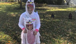 In this file photo,ten-year-old Cameron Fox and her 4-year-old sister, Lexi, of Brookfield, Ill., are dressed as unicorns for Halloween with plastic face shields to protect against COVID-19, as they visit the home of family friends in nearby River Forest, Ill., on Saturday, Oct. 31, 2020.  While this year many Americans are eager to resume Halloween traditions shelved because of the pandemic, an ongoing supply-chain crunch has resulted in party-supply stores nationwide running out of the most coveted mass-produced costumes.  (AP Photo/Don Babwin)  **FILE**