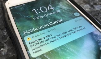 An emergency alert regarding the coronavirus pandemic is displayed on a cellphone Friday, Oct. 30, 2020, in Rio Rancho, N.M. The alert was sent out to New Mexicans across the state urging them to stay home amid a surge in COVID-19 cases and record-high hospitalizations. The state also surpassed the 1,000 mark for deaths related to the virus. (AP Photo/Susan Montoya Bryan)