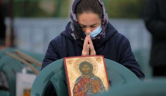 An Orthodox worshiper, wearing a mask for protection against the COVID-19 infection, prays during a religious service, on the first day of the Saint Dimitrie Basarabov pilgrimage in Bucharest, Romania, Sunday, Oct. 25, 2020. (AP Photo/Vadim Ghirda)