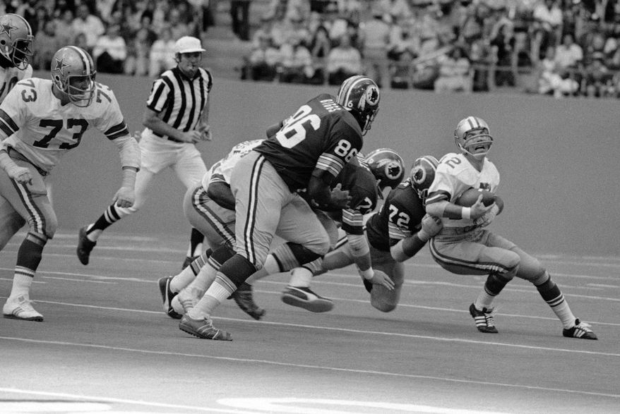 Dallas Cowboys' quarterback Roger Staubach grimaces as he loses yards during second quarter action Nov. 28, 1974 in Irving, Texas. Making the tackle is Washington Redskins Verlon Biggs (86), Ron McDole (79) and Diron Talbert (72). (AP Photo/Ferd Kaufman)  **FILE**