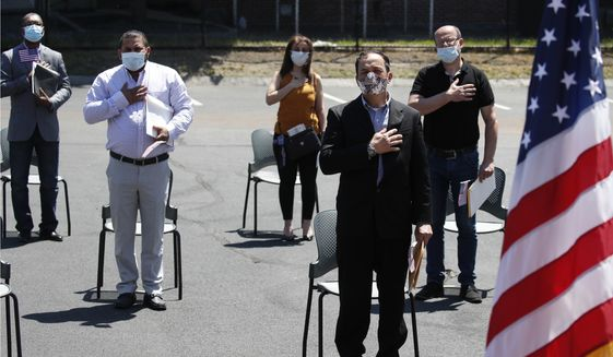 In this June 4, 2020, file photo, new citizens, socially distanced, recite the pledge of allegiance outside the U.S. Citizenship and Immigration Services building in Lawrence, Mass. (AP Photo/Elise Amendola, File)