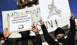 "Protesters hold placards with a depiction of Eiffel Tower in Paris, right, marked with a shoe stamp a sign of disrespect, and one, left with a slogan reading in Turkish: ""May my mother and father be sacrificed in your name, Prophet!"", during a protest by members of Islamic groups against France in Istanbul, Sunday, Nov. 1, 2020.  There had been tension between France and Turkey after Turkish President Recep Tayyip Erdogan said France's President Emmanuel Macron needed mental health treatment and made other comments that the French government described as unacceptably rude. Erdogan questioned his French counterpart's mental condition while criticizing Macron's attitude toward Islam and Muslims. (AP Photo)"