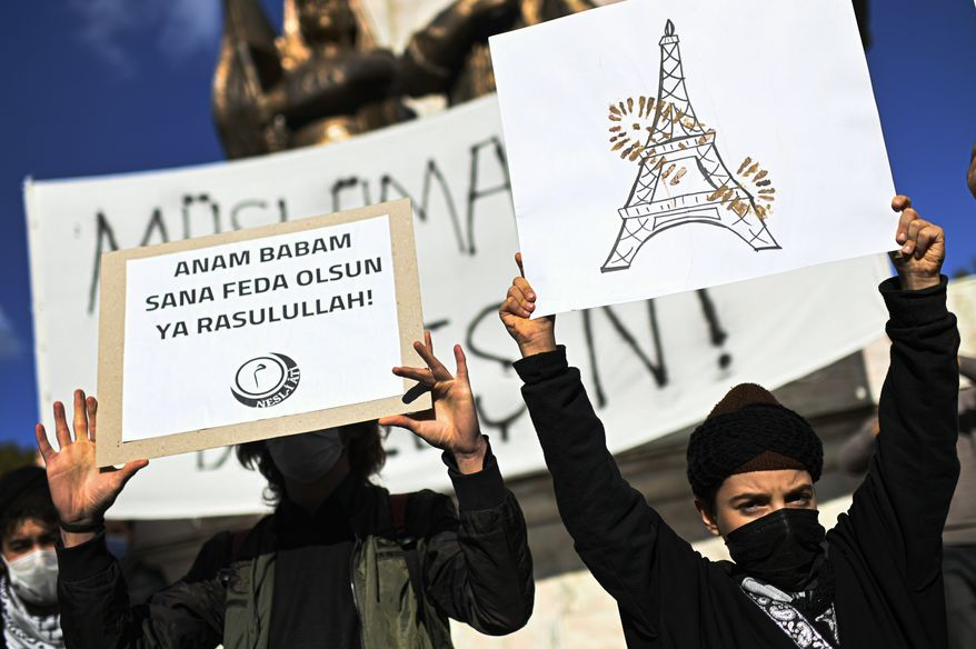 """Protesters hold placards with a depiction of Eiffel Tower in Paris, right, marked with a shoe stamp a sign of disrespect, and one, left with a slogan reading in Turkish: """"May my mother and father be sacrificed in your name, Prophet!"""", during a protest by members of Islamic groups against France in Istanbul, Sunday, Nov. 1, 2020.  There had been tension between France and Turkey after Turkish President Recep Tayyip Erdogan said France's President Emmanuel Macron needed mental health treatment and made other comments that the French government described as unacceptably rude. Erdogan questioned his French counterpart's mental condition while criticizing Macron's attitude toward Islam and Muslims. (AP Photo)"""