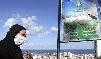 A woman walks past posters promoting the vote for the upcoming referendum, Tuesday, Oct.27, 2020 in Algiers. A vote on a new constitution in Algeria will take place on Nov.1, 2020. (AP Photo/Fateh Guidoum)