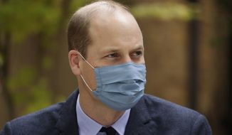 """In this Oct. 20, 2020, file photo, Britain's Prince William, wearing a face covering to curb the spread of the coronavirus, meets pharmacist Joyce Duah as he and his wife Kate the Duchess of Cambridge visit St. Bartholomew's Hospital in London to mark the launch of the nationwide """"Hold Still"""" community photography project. Prince William tested positive for the coronavirus, apparently around the same time as his father Prince Charles earlier this year, BBC reported. The report cited unidentified palace sources and The Sun newspaper, which said William kept his telephone and video engagements without revealing his diagnosis because he didn't want to worry anyone. (AP Photo/Matt Dunham, Pool, File)"""