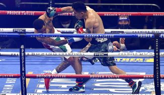 Gervonta Davis, left, is knocked down by Leo Santa Cruz during the first round of a boxing bout Saturday, Oct. 31, 2020, in San Antonio. (AP Photo/Ronald Cortes)