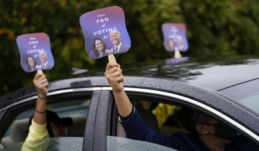 """Biden supporters hold up fans during a """"Souls to the Polls"""" drive-in rally for Democratic presidential candidate former Vice President Joe Biden at Sharon Baptist Church, Sunday, Nov. 1, 2020. (AP Photo/Andrew Harnik)"""
