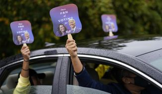 "Biden supporters hold up fans during a ""Souls to the Polls"" drive-in rally for Democratic presidential candidate former Vice President Joe Biden at Sharon Baptist Church, Sunday, Nov. 1, 2020. (AP Photo/Andrew Harnik)"