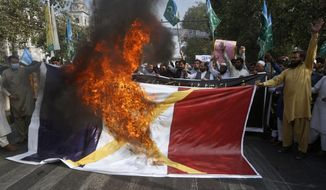 """FILE - In this Oct.30, 2020 file photo, supporters of religious group burn a representation of a French flag during a rally against French President Emmanuel Macron and republishing of caricatures of the Prophet Muhammad they deem blasphemous, in Lahore, Pakistan. A spotlight of suspicion encircled Muslims again even before the latest acts of extremist violence, including two beheadings. French President Emmanuel Macron has forged ahead with a plan to rid Islam in France of extremists, part a project he labels """"separatism,"""" a term that makes some Muslims wince. (AP Photo/K.M. Chaudary, File)"""