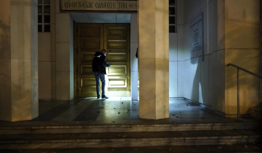 A police officer searches for clues after a priest was shot, Saturday Oct. 31, 2020, in the city of Lyon, central France. A Greek Orthodox priest was shot while he was closing his church in the French city of Lyon, and authorities locked down part of the city to hunt for the assailant. The priest, a Greek citizen, is in a local hospital with life-threatening injuries after being shot twice in the abdomen. (AP Photo/Laurent Cipriani)