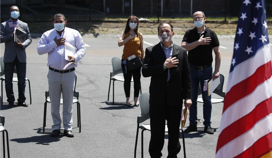 In this June 4, 2020, file photo, new citizens, socially distanced, recite the pledge of allegiance outside the U.S. Citizenship and Immigration Services building in Lawrence, Mass.  (AP Photo/Elise Amendola, File) **FILE**