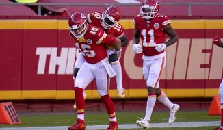Kansas City Chiefs quarterback Patrick Mahomes (15) gives wide receiver Tyreek Hill (10) a ride on his back to the bench as wide receiver Demarcus Robinson (11) looks on following Hill's touchdown catch in the second half of an NFL football game against the New York Jets on Sunday, Nov. 1, 2020, in Kansas City, Mo. (AP Photo/Jeff Roberson)