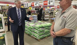 FILE - In this May 7, 2020 file photo, Gov. Mike Parson, left, talks with store manager Ron Schuman, right, during a tour of the Orscheln Farm & Home store in Jefferson City, Mo. Parson was visiting the store to promote the end of a stay-at-home order he had issued because of the coronavirus pandemic. Midwest governors credit their lack of restrictions for low unemployment rates, but economists and others say other factors might be more important in the states low jobless rates. (AP Photo/David A. Lieb, File)