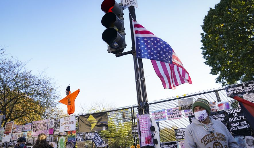 Pedestrians stand beside a fence covered in protest signs on the north side of the White House, Monday, Nov. 2, 2020, on a section of 16th Street renamed Black Lives Matter Plaza in Washington, on the day before the U.S. election. (AP Photo/John Minchillo)