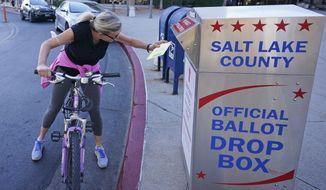 Debbie Sorensen inserts her ballot into a drops box Monday, Nov. 2, 2020, in Salt Lake City. (AP Photo/Rick Bowmer)