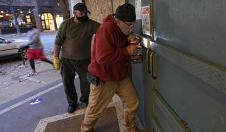 Ianni Stanciu, right, puts screws in a piece of lumber as he works to board up a Patagonia store in downtown Seattle, Monday, Nov. 2, 2020, the day before Election Day. Many businesses in the city boarded up windows Monday as a precaution against possible protests or violence on Election Day or the days following. (AP Photo/Ted S. Warren)