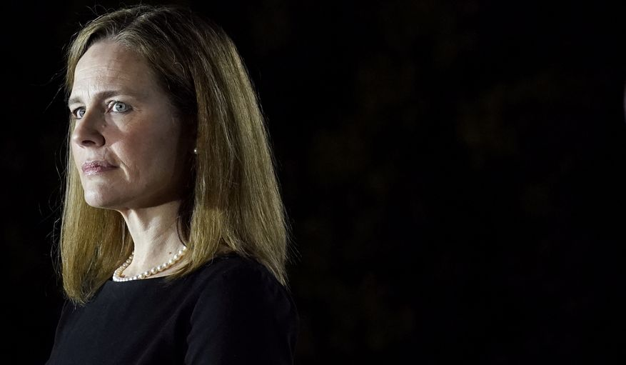 In this Oct. 26, 2020, file photo Amy Coney Barrett, listens as President Donald Trump speaks before Supreme Court Justice Clarence Thomas administers the Constitutional Oath to Barrett on the South Lawn of the White House in Washington, after she was confirmed by the Senate. (AP Photo/Patrick Semansky, File)