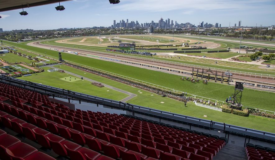 Empty stands are seen during the Finish of Race 3 prior to the Melbourne Cup horse race at Flemington Racecourse in Melbourne, Australia, Tuesday, Nov. 3, 2020. (AP Photo/Andy Brownbill)