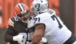 Cleveland Browns defensive end Myles Garrett, left, and Las Vegas Raiders offensive tackle Denzelle Good collide during the first half of an NFL football game, Sunday, Nov. 1, 2020, in Cleveland. Garrett injured his knee in the first quarter in the Browns 16-6 loss to the Raiders. (AP Photo/David Richard)