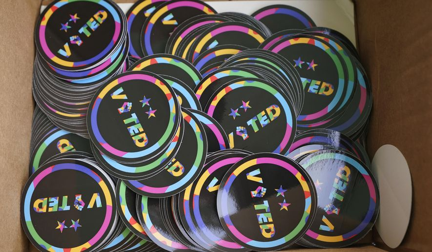 "A box of stickers that read ""Voted"" and were specially designed by the Seattle Sounders MLS soccer team are shown during a get-out-the-vote event at a Starbucks store, Tuesday, Oct. 27, 2020, in Seattle's White Center neighborhood. Washington is a vote by mail state, and thousands of ballots have already been mailed back, dropped off in boxes, or cast in person. (AP Photo/Ted S. Warren)"
