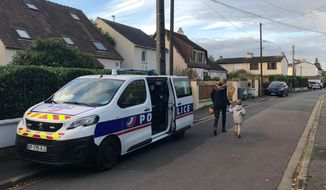 A woman holds her child by the hand on their way to the school in Conflans-Sainte-Honorine, northwest of Paris, Monday Nov.2, 2020. All schools in France hold a minute of silence at 11h to honor the teacher beheaded in Conflans-Sainte-Honorine for showing his class caricatures of Islam's prophet for a debate on free expression. (AP Photo/Oleg Cetinic)