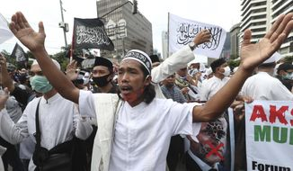 Indonesian Muslims protester shout slogans during an anti-France rally outside the France embassy in Jakarta, Indonesia, Monday, Nov. 2, 2020. Indonesian Muslims marched to the heavily guarded France Embassy in Indonesia's capital on Monday to protest France's president and his staunch support of secular laws that deem caricatures depicting the Prophet Muhammad as protected speech.(AP Photo/Achmad Ibrahim)