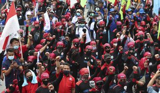 Labor demonstrators shout slogans during a protest against new Job Creation Law in Jakarta, Indonesia, Monday, Nov. 2, 2020. Thousands of workers in Indonesia on Monday continued their protests against the country's new jobs law that critics say will erode labor rights and weaken environmental protections.(AP Photo/Achmad Ibrahim)