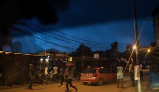 People cross a street at Blockhaus neighborhood during the dusk in Abidjan, Ivory Coast, Sunday, Nov. 1, 2020. Ivory Coast residents braced for more unrest Sunday as election officials began releasing the first results from the country's presidential election and opponents of President Alassane Ouattara stepped up their criticism of his quest for a third term. (AP Photo/Leo Correa)