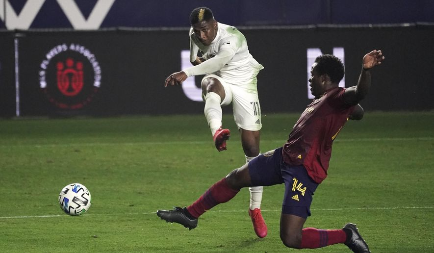 Los Angeles Galaxy's Yony Gonzalez, center, shoots under pressure by Real Salt Lake's Nedum Onuoha during the first half of an MLS soccer match, Sunday, Nov. 1, 2020, in Carson, Calif. (AP Photo/Jae C. Hong)