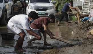 Residents use wood to clear out a mud-covered road after floodwaters caused by Typhoon Goni rose inside their village in Batangas city, Batangas province, south of Manila, Philippines on Monday, Nov. 2, 2020. Super Typhoon Goni left wide destruction as it slammed into the eastern Philippines with ferocious winds early Sunday and about a million people have been evacuated in its projected path. (AP Photo/Aaron Favila)