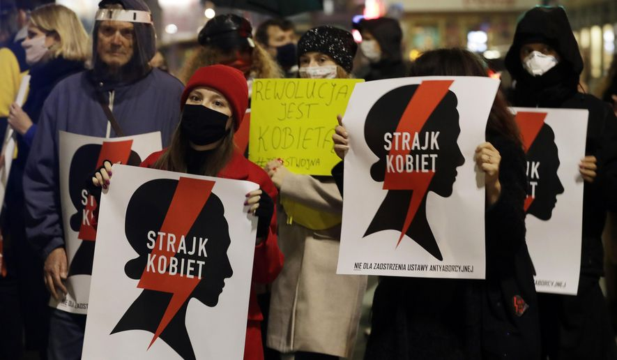 "Protesters hold signs reading in Polish ""women's strike"" as they block a crossing in downtown Warsaw, Monday, Nov. 9, 2020, on the 12th straight day of anti-government protests that were triggered by the tightening of Poland's strict abortion law and are continuing despite a anti-COVID-19 ban on public gatherings. (AP Photo/Czarek Sokolowski)"