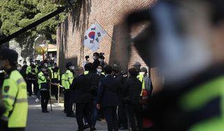 South Korean police officers stand outside a residence of former President Lee Myung-bak in Seoul, South Korea, Monday, Nov. 2, 2020. Lee was sent back to prison on Monday, four days after the country's top court upheld a 17-year prison term on him over corruption crimes. (AP Photo/Lee Jin-man)
