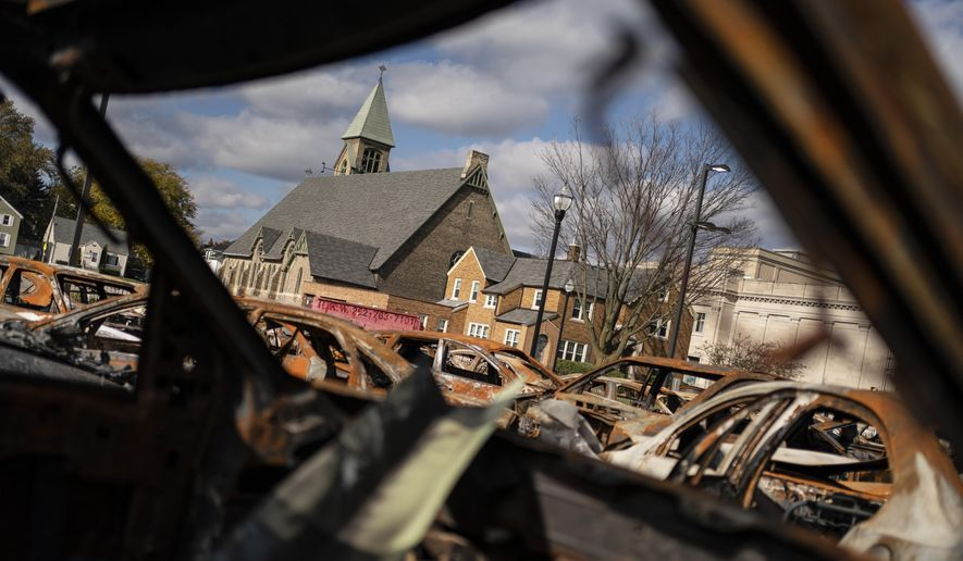 A church building is framed by the remains of burnt vehicles in Kenosha, Wis., Friday, Oct. 30, 2020. The trouble in Kenosha began on Aug. 23 when a Kenosha police officer, responding to a call about a domestic dispute, was caught on video shooting Jacob Blake repeatedly in the back at close range. Blake, a Black man, survived but is partially paralyzed. The August shootings have spurred a spike in political involvement in Kenosha, with the formation of activism and waves of new voters signing up. (AP Photo/Wong Maye-E)