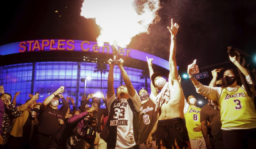 FILE - In this Oct. 11, 2020, file photo, Los Angeles Lakers fans celebrate outside of Staples Center in Los Angeles, after the Lakers defeated the Miami Heat in Game 6 of basketball's NBA Finals to win the championship. Gatherings large and small are likely to blame for a slight uptick in daily coronavirus cases in California's largest county. That's according to a top Los Angeles County health official who warned Monday, Nov. 2, 2020, that upcoming holiday parties pose a risk for the renewed spread and a spike in hospitalizations. (AP Photo/Christian Monterrosa, File)