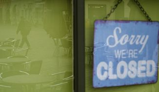 """""""Sorry we re closed"""" is written on a sign hanging on the door of a coffee shop where the unoccupied tables and chairs are reflected in the glass pane in Quedlinburg, Germany, Monday, Nov.2, 2020. Since midnight the four-week partial lockdown has been in effect in Saxony-Anhalt. The federal and state governments want to significantly reduce social contacts in Germany in November in order to get a grip on the recently rapidly increasing corona numbers before the Advent season if possible. (Klaus-Dietmar Gabbert/dpa via AP)"""