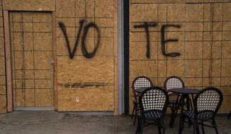 """The word """"Vote"""" is spray painted on plywood of a boarded-up store on Election Day Tuesday, Nov. 3, 2020, in Los Angeles. The scourge of a global pandemic produced an election season like no other in the U.S., persuading record numbers of Americans to cast their ballots early, forcing states to make changes to long-established election procedures and leading to hundreds of lawsuits over how votes will be cast and which ballots will be counted. (AP Photo/Jae C. Hong)"""