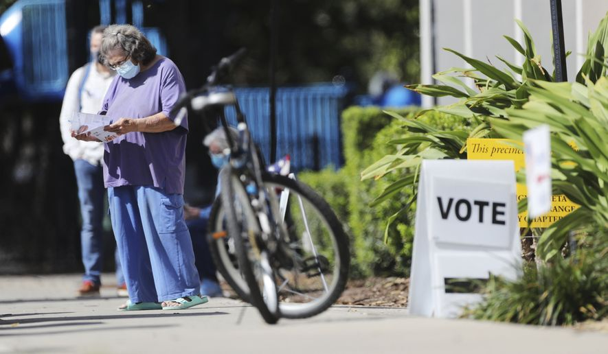 Citizens leave Precinct 629 at the John H. Jackson Community Center -- Polling places in Orange County on Election Day, Tuesday, Nov. 3, 2020. (Ricardo Ramirez Buxeda/ Orlando Sentinel via AP)