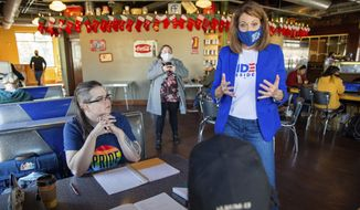 Rep. Cindy Axne, D-Iowa, speaks with Jean Riehm and Julian Seay in Des Moines, Iowa, Tuesday, Nov. 3, 2020. (Zach Boyden-Holmes/The Des Moines Register via AP)
