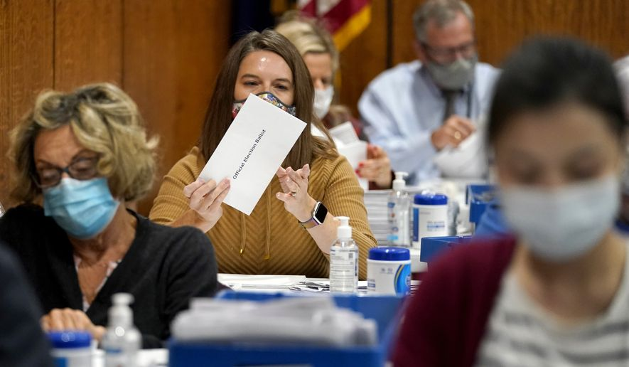 An election worker opens up a mail-in ballot before it's counted in the 2020 general election at the Dauphin County Administration Building, Tuesday, Nov. 3, 2020, in Harrisburg, Pa. (AP Photo/Julio Cortez)