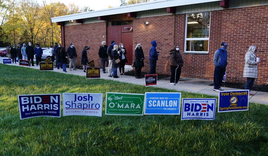 People line up outside a polling place to vote in the 2020 general election in the United States, Tuesday, Nov. 3, 2020, in Springfield, Pa. (AP Photo/Matt Slocum)