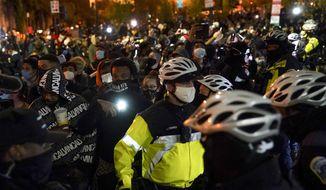 District of Columbia Metropolitan Police patrol as demonstrators march through the streets near the White House, Tuesday, Nov. 3, 2020, in Washington. (AP Photo/John Minchillo)