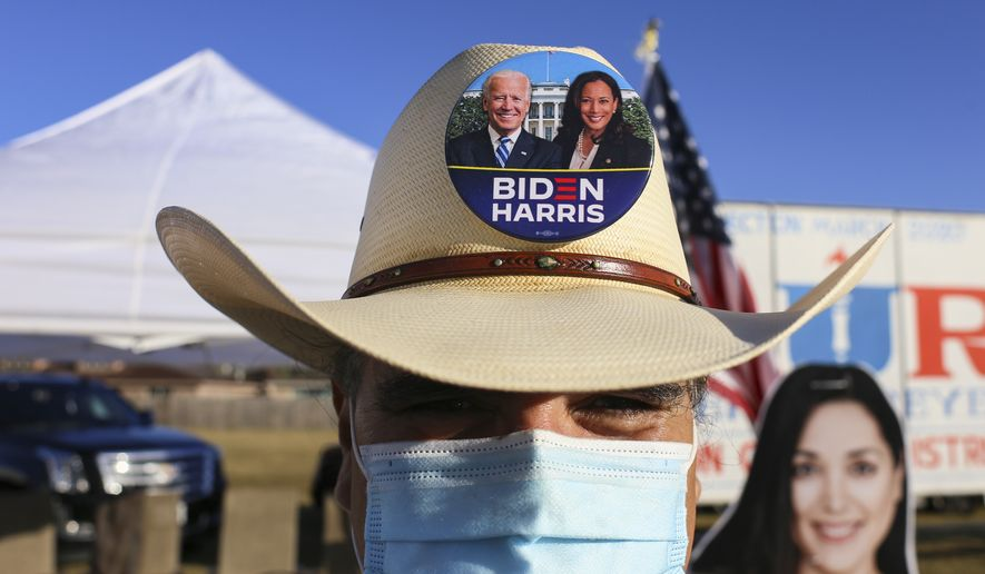 Tito Mata wears a Biden-Harris campaign button pinned to his hat, Tuesday, Nov. 3, 2020, as he campaigns outside the polling location at Burns Elementary School in Brownsville, Texas. (Denise Cathey/The Brownsville Herald via AP)